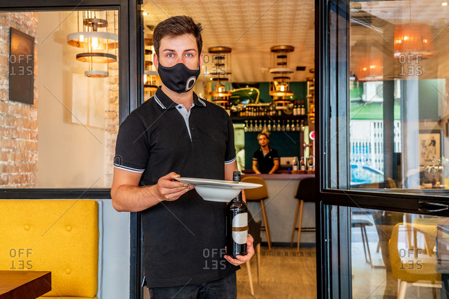 Serious waiter standing with bottle of beer and plate in cafe while looking at camera
