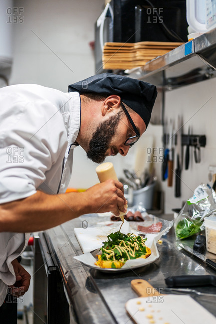 Side view of busy male chef in uniform adding sauce on top of dish with greenery while working in kitchen of cafe