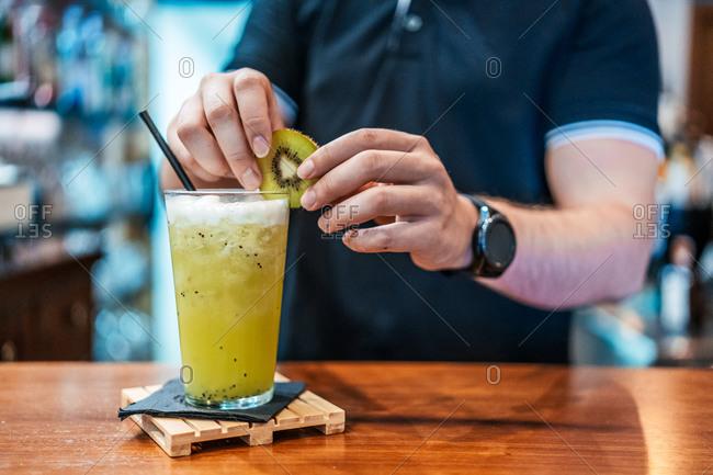 Anonymous bartender garnishing glass with nonalcoholic cocktail with slice of fresh kiwi fruit