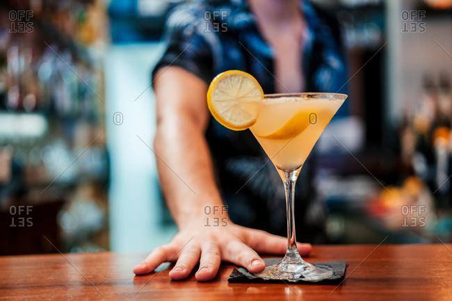 Crop barman pouring fresh alcohol cocktail in glass goblet placed on counter in bar