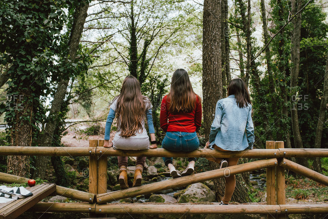 Back view of company of unrecognizable female friends sitting on wooden fence in forest and enjoying nature during summer vacation in Valle del Jerte