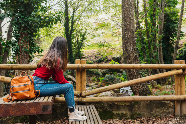 Side view of anonymous female tourist sitting on old bench in woods and admiring magnificent nature in Valle del Jerte