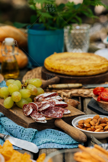 Various delicious food arranged on shabby wooden table in recreational area for picnic in Valle del Jerte