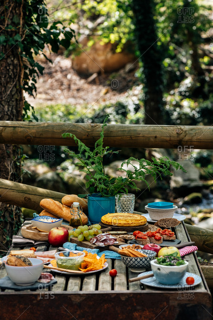 From above of old wooden table with assorted dishes served for cozy picnic in forest in Valle del Jerte