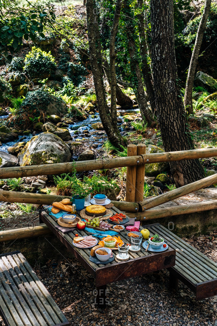High angle of old wooden table with assorted dishes served for cozy picnic in forest in Valle del Jerte