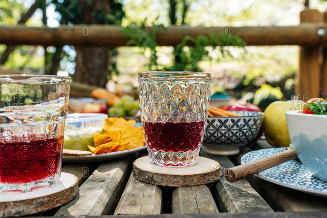 Glasses with delicious grape juice served on wooden table with various food for picnic in forest in Valle del Jerte