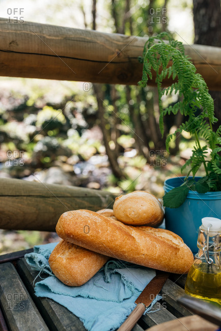 Loaves of tasty bread placed on wooden table for picnic in woods in Valle del Jerte