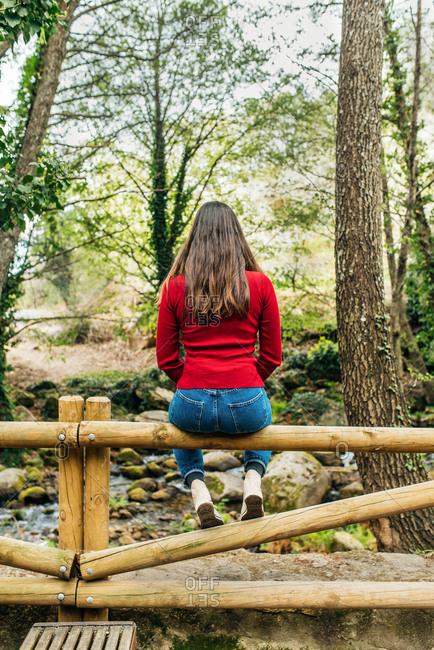 Back view of anonymous female tourist sitting on old bench in woods and admiring magnificent nature in Valle del Jerte