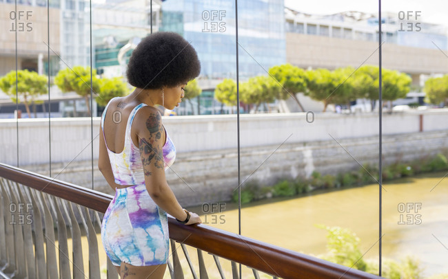 Side view of relaxed African American female standing on suspension bridge and admiring view of river in city during stroll on sunny day