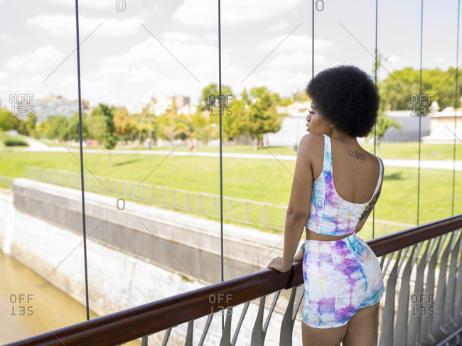 Back view of relaxed African American female standing on suspension bridge and admiring view of river in city during stroll on sunny day