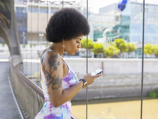 Side view of African American female with Afro hairstyle and in fancy outfit standing on bridge in city and reading messages on social media via cellphone