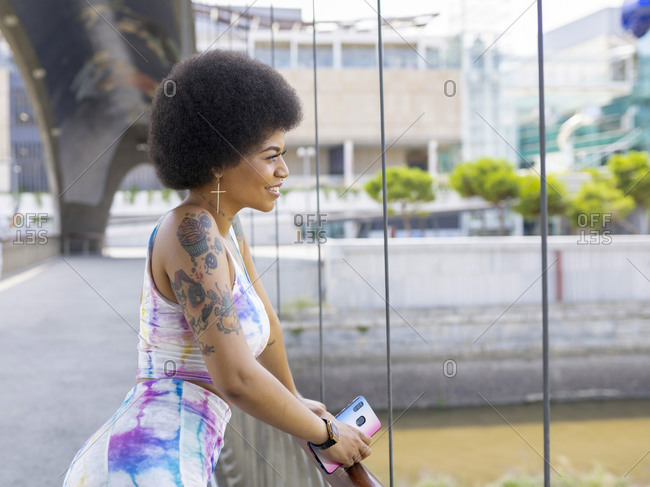 Side view of happy African American female standing on suspension bridge and admiring view of river in city during stroll on sunny day