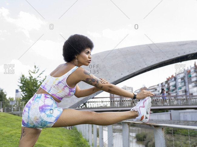 Side view of confident black sportswoman stretching legs while doing forward bend and leaning on metal fence before workout in city