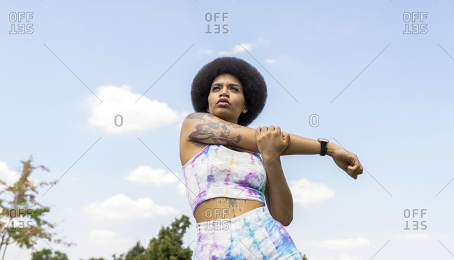 Low angle of African American female athlete stretching arms while warming up before training in city and looking away