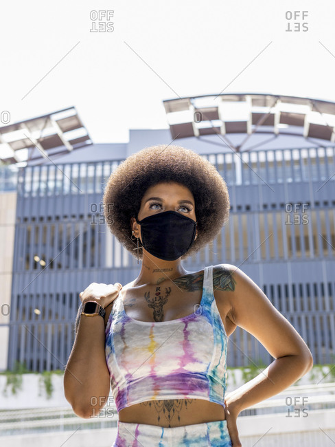 Confident African American female in medical mask and fashionable summer outfit standing in urban area in city during coronavirus outbreak