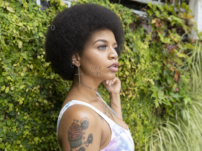 Side view of stylish African American woman with tattoos and piercing standing in urban park in summer and looking away