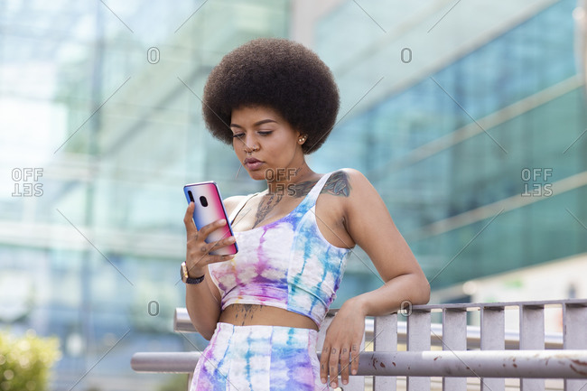 Thoughtful African American stylish female with Afro hairstyle standing on street and surfing Internet on smartphone