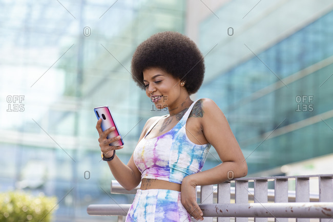 African American stylish female with Afro hairstyle standing on street and surfing Internet on smartphone