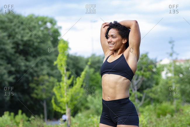 Delighted African American muscular female stretching arms and warming up before training in park while looking away