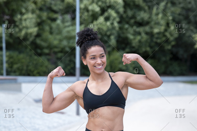 Delighted African American athletic female with strong arms showing biceps and looking away