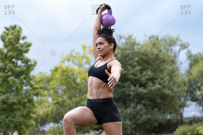 Determined African American muscular sportswoman doing kettlebell snatch exercise during functional workout in park