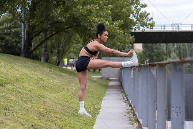 Side view of flexible African American female athlete standing near metal railing and stretching legs while doing forward bend before workout