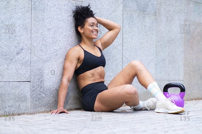Positive black athletic female in sportswear sitting on sidewalk with kettlebell and having break during functional workout in city