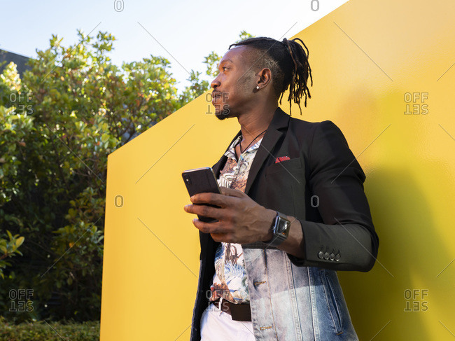 African American entrepreneur in fancy clothes standing near yellow wall in city and browsing cellphone while working remotely