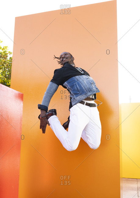 Low angle of carefree African American male in fancy outfit in moment of jumping above ground near vibrant orange wall in city