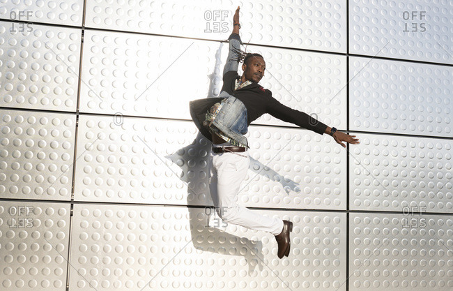 Side view of well dressed ethnic male entrepreneur jumping near urban building with outstretched arms and looking away