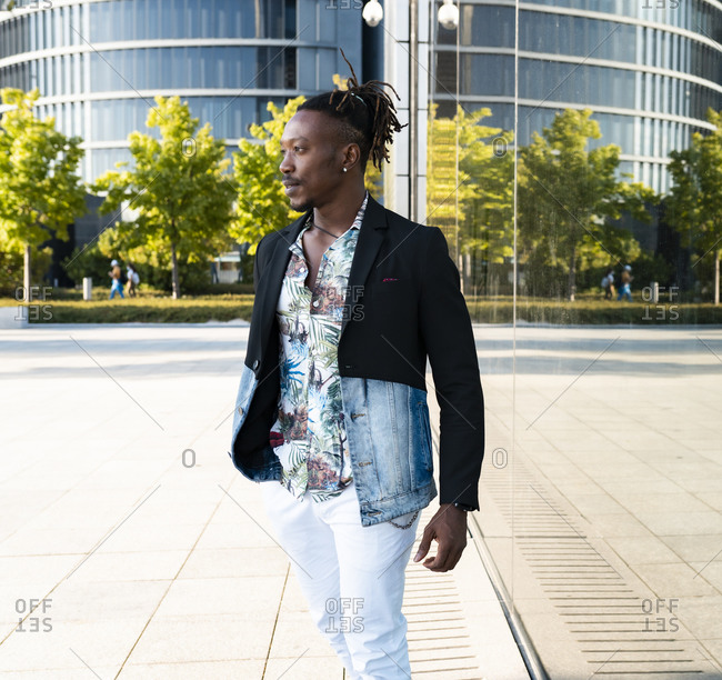 Determined black male wearing fancy clothes walking along glass building in city and looking away