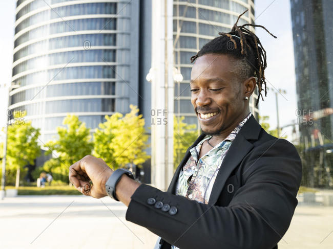 Low angle side view of positive African American male entrepreneur looking at wristwatch and checking time while standing in city and waiting for meeting