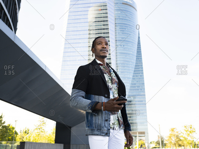 Low angle of stylish African American male executive manager standing with cellphone on street in city center and looking away