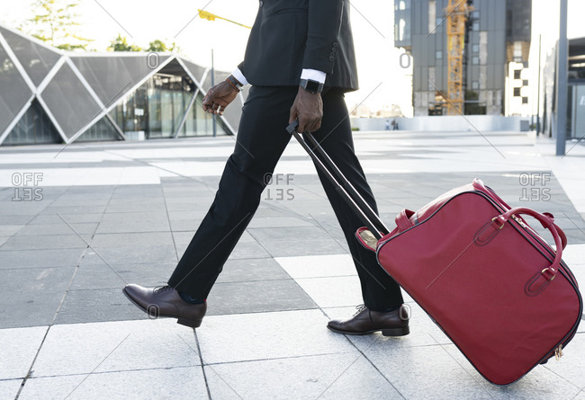 Side view of African American male entrepreneur wearing classy suit walking with suitcase towards airport for departure