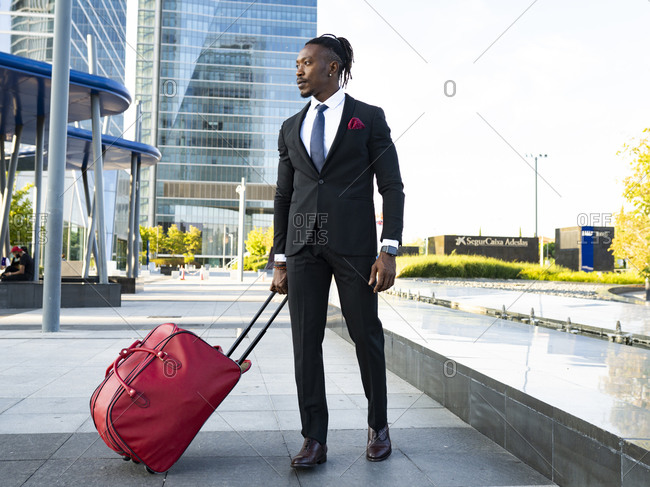 African American male entrepreneur wearing classy suit walking with suitcase towards airport for departure