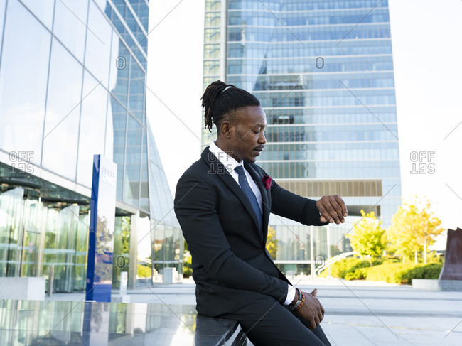 Side view of serious African American male entrepreneur looking at wristwatch and checking time while sitting in city and waiting for meeting