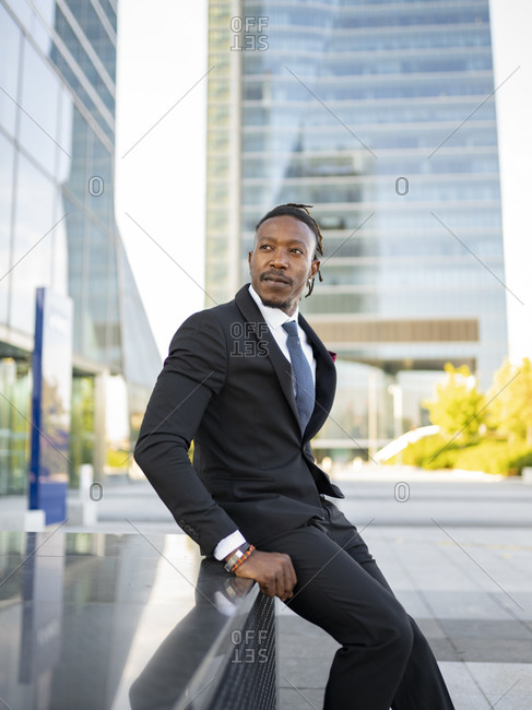 Side view of confident black male executive manager in formal suit sitting on fence in megalopolis and looking away