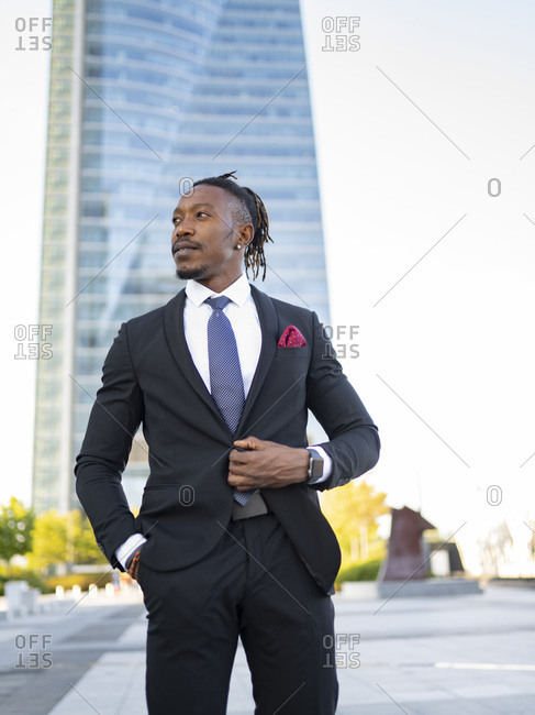Cheerful African American male entrepreneur wearing elegant suit walking along glass office building in city center and looking away