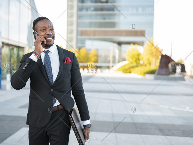 Delighted African American male entrepreneur in formal suit walking with laptop along street and having conversation on smartphone while discussing business project and looking away