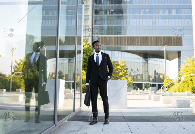 Serious African American male entrepreneur wearing elegant suit walking along glass office building in city center and looking away