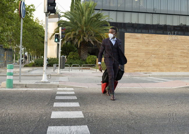 Serious black male entrepreneur wearing medical mask crossing road in city while walking with bags towards airport during coronavirus epidemic