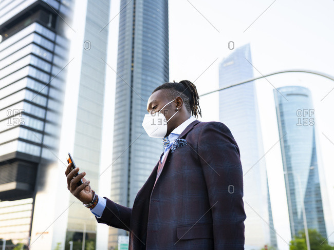 Side view of determined African American male entrepreneur in protective mask in downtown during coronavirus browsing smartphone on street