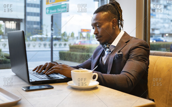 Side view of concentrated African American businessman in suit sitting at table with coffee in cafe and typing on netbook while working on remote project