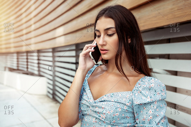 Young ethnic female in stylish blouse talking smartphone while standing near shuttered window of modern building
