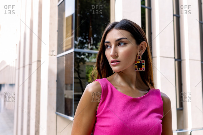 Young slim ethnic female in stylish pink overall with elegant earrings and bracelet standing against blue wall of contemporary building