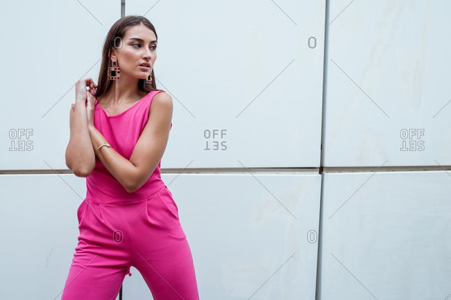 From below of young slim ethnic female in stylish pink overall with elegant earrings and bracelet standing against blue wall of contemporary building