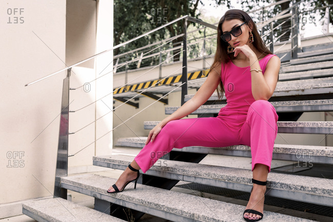 Low angle of attractive young female dressed in bright pink overall and stylish sunglasses and high heeled sandals sitting on stairs near modern urban building
