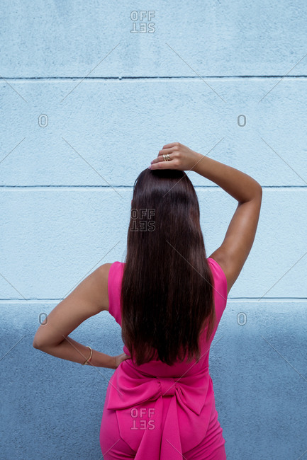 Back view of unrecognizable slim brunette with gorgeous long hair dressed in elegant pink outfit standing with hand on head against blue wall