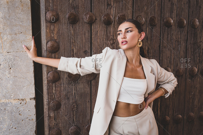 Delightful slim ethnic female model with perfect makeup wearing stylish light suit standing against weathered wooden door of urban building