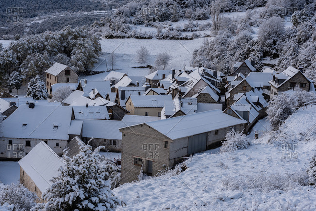 Amazing scenery of village with residential houses located in highland valley in Pyrenees in winter
